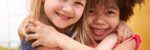 Two prepubescent girls hugging photo from Brest Cancer Prevention Partners